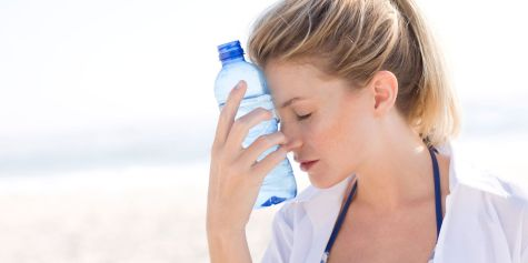 landscape-1496143599-exhausted-woman-in-heat-holding-water-bottle-to-face